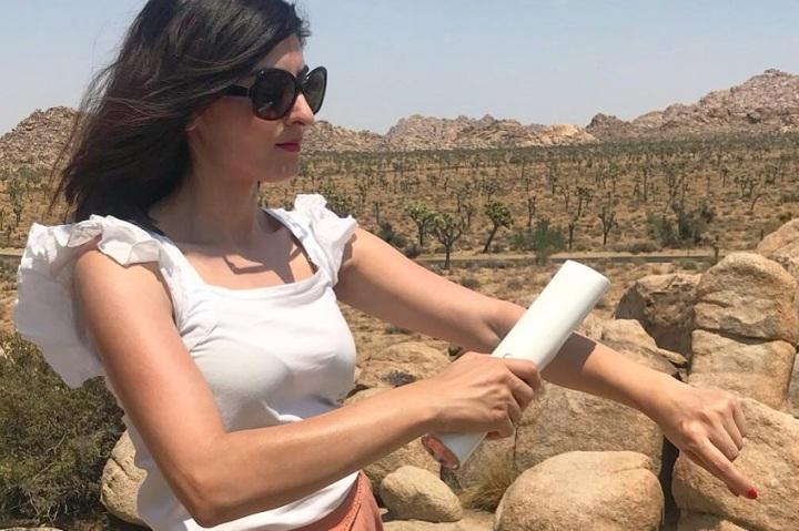 Eine junge Frau benutzt das innovative Sprühgerät zum Auftragen von Sonnenschutzmittel.